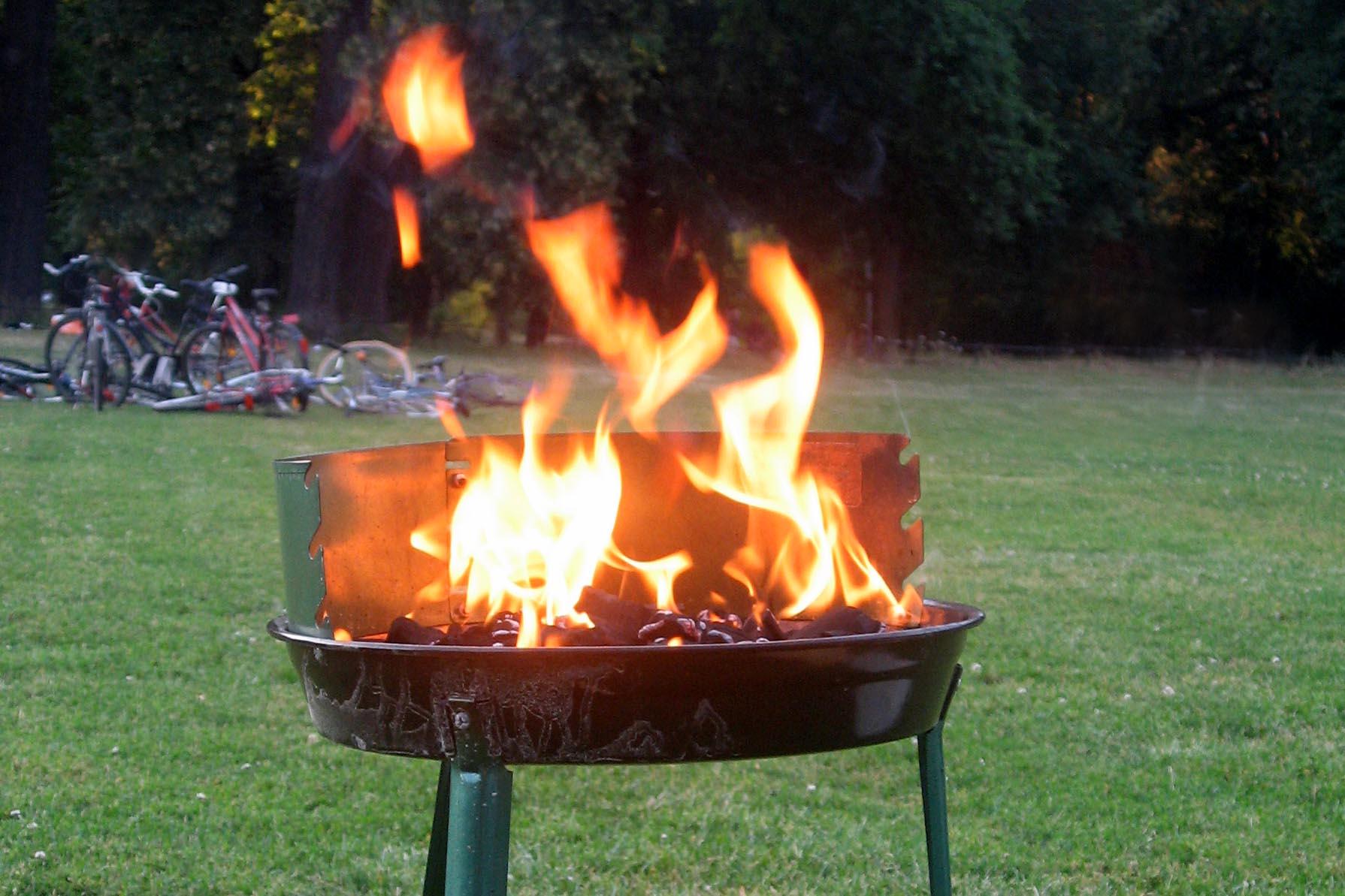 Flammen auf einem Holzkohlegrill, der gerade angezündet wird.